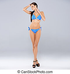 Sexy brunette posing in blue swimsuit while isolated on gray...