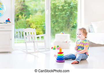 Smiling toddler girl playing with a pyramid toy in a white...