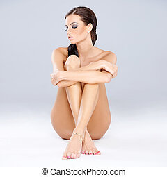 Young sexy brunette sitting while isolated