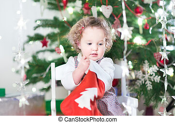 Cute toddler girl checking her Christmas stocking under a...