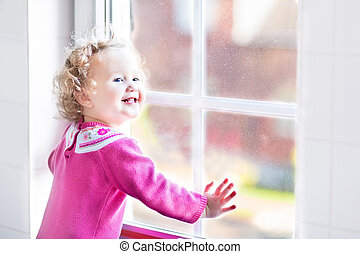 Beautiful little girl watching out of a window with autumn...