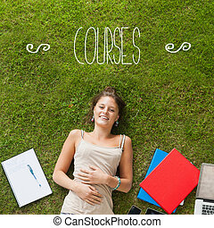 Courses against pretty student lying on grass - The word...