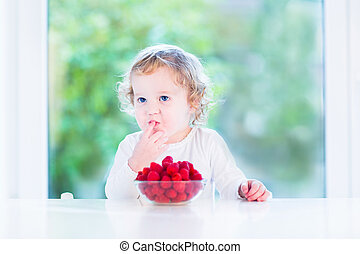 Funny toddler girl eating raspberries in the morning at a big wi