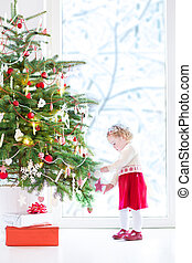 Cute little toddler girl wearing a red festive dress decorating