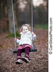 Adorable toddler girl with curly hair wearing a white warm...