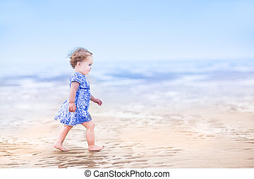 Cute toddler girl in a blue dress walking on a beach at...
