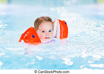 Happy toddler girl having fun in a swimming pool