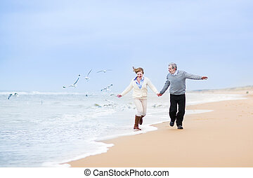 Happy mature couple running at a beautiful winter beach with...