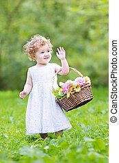 Funny toddler girl playing with a flower basket on Easter...