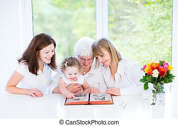 Happy grandmother watching black and white photo album with...
