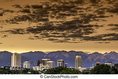 Skyline of Utah city with clouds - Morning orange sky over...