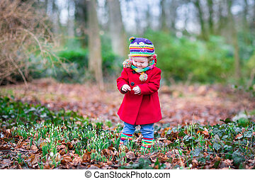 Cute little toddler girl in a red coat playing with beautiful sn