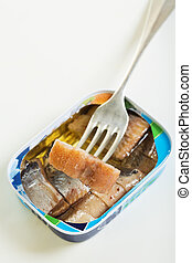 Tin and slice of herring on a fork.
