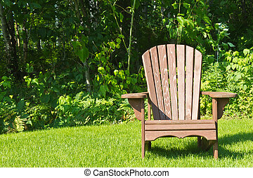 Adirondack summer lawn chair outside on the green grass -...