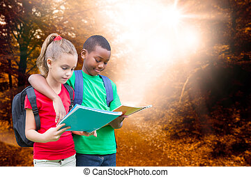 Composite image of cute pupils reading against forest trail