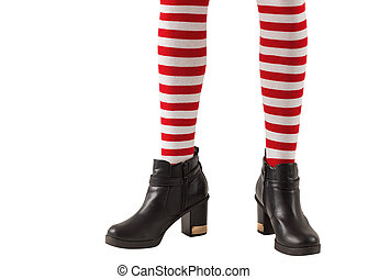 Lower half of girl wearing stripey socks and boots on white...