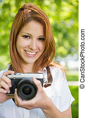 Pretty redhead taking a photo in the park on a sunny day