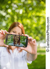 Pretty redhead taking a selfie on her phone in the park on a...