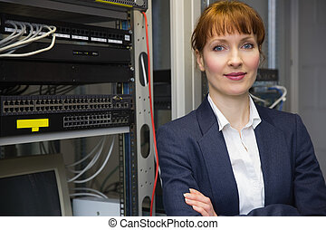 Pretty computer technician smiling at camera beside server...