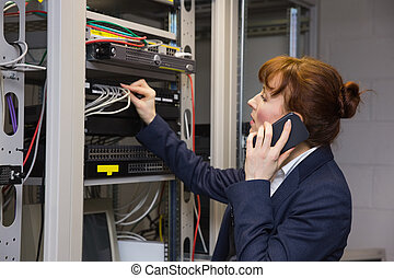 Pretty computer technician talking on phone while fixing...