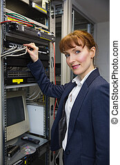 Pretty computer technician smiling at camera while fixing...
