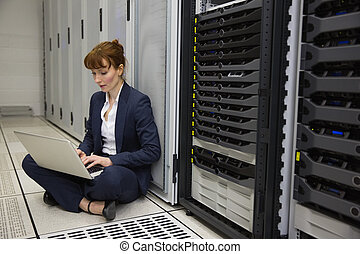 Technician sitting on floor beside server tower using laptop...