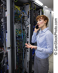 Technician talking on phone while analysing server in large...