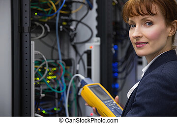 Happy technician using digital cable analyzer on server in...