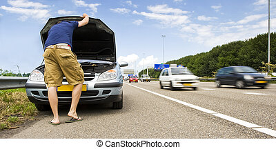 Mortorway car trouble - Man staring down at the engine of...
