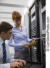 Team of technicians using digital cable analyser on servers...