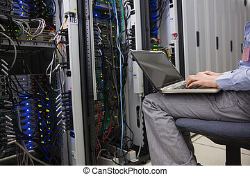 Technician sitting on swivel chair using laptop to diagnose...