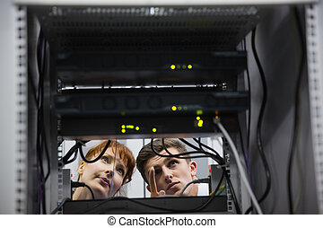 Team of technicians talking and looking at server in large...