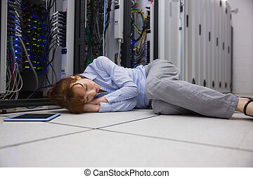 Exhausted technician sleeping on the floor in large data...