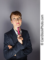 Businesswoman holding glasses and thinking