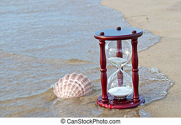 sand timer with seashell - Seashell and sand timer in water...