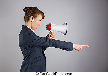 Angry businesswoman shouting through megaphone and pointing...