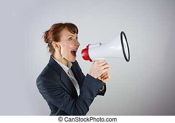 Smiling businesswoman shouting through megaphone on grey...