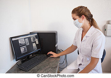 Dental assistant looking at x-rays on computer at the dental...