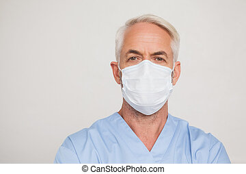 Dentist in surgical mask looking at camera at the dental...