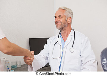 Dentist shaking hands with his patient at the dental clinic