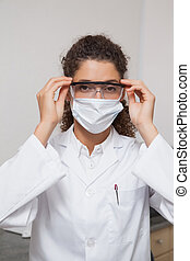 Dentist putting on protective glasses looking at camera at...