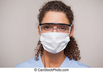 Dentist in surgical mask and protective glasses looking at...