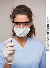 Dentist in surgical mask and scrubs holding tool at the...