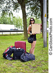 Hitch hiking woman - Young woman hitch hiking with a lot of...