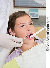 Pediatric dentist examining a little girls teeth in the...
