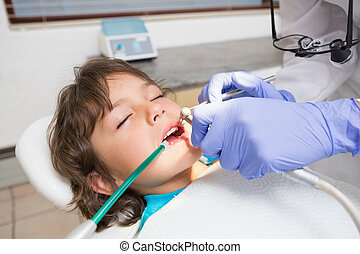 Pediatric dentist examining a little boys teeth in the...
