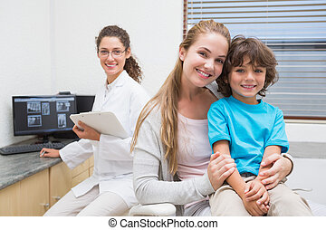 Pediatric dentist smiling at camera with little boy and his...