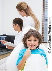 Little boy smiling at camera with mother and dentist in backgrou