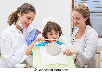 Pediatric dentist showing little boy how to brush teeth with...