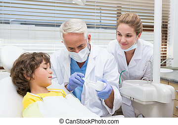 Pediatric dentist showing little boy how to brush his teeth